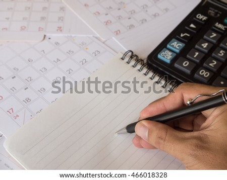 Hand with pen writing on notebook and calculator on calendar