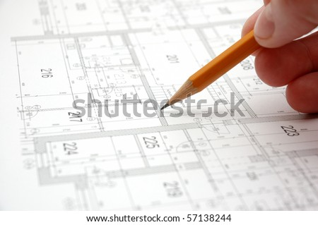 Hand with pencil on building drawing