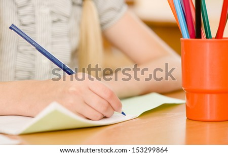 hand with pencil writing in a notebook - stock photo