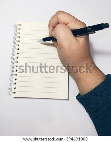 Hand with pencil writing in open book - stock photo