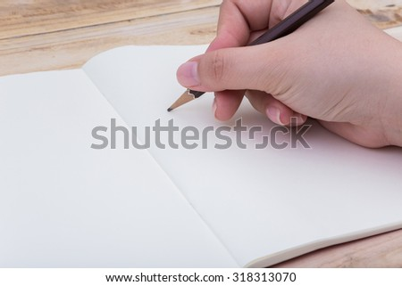 hand with pencil writing to a blank notebook on wooden table