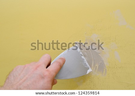 Hand with putty knife repair damaged wall - stock photo