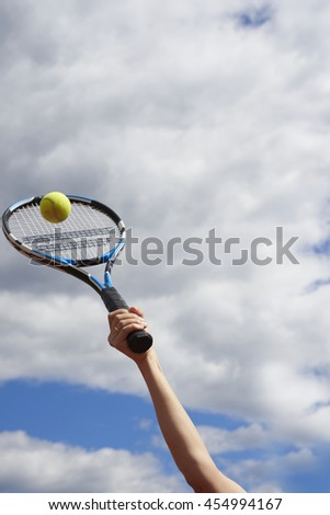 hand with racket and ball against the sky