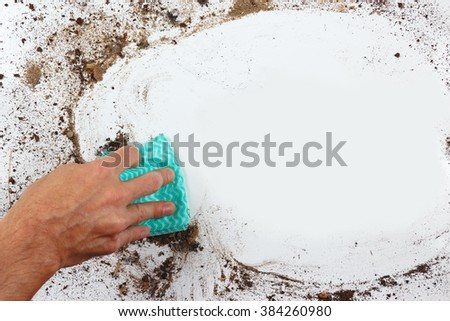 Hand with rag cleans a dirty surface - stock photo