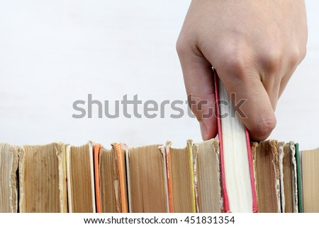 hand with red book in the library / necessary literature for education - stock photo