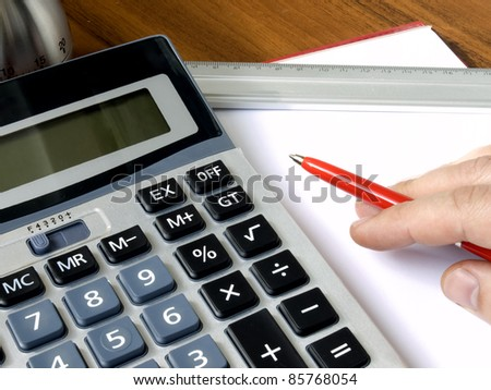 Hand with red holding a ball pen, timer, measuring ruler, sheet of a paper laying on a desk
