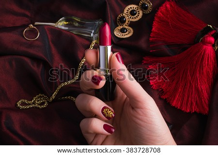 hand with red nail polish, perfume, lipstick, decoration on burgundy background