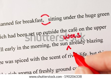 Hand with red pen proofreading a novel  - stock photo