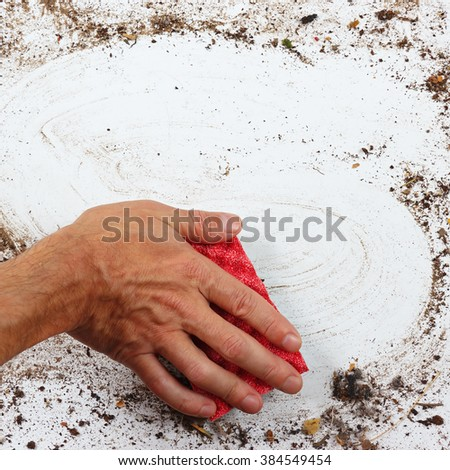 Hand with red sponge wiping a heavily dirty surface - stock photo