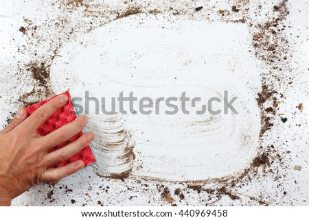 Hand with red sponge wiping a very dirty surface - stock photo