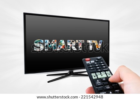 Hand with remote control aiming modern Smart TV device - stock photo