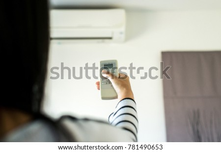 Hand with remote control of air conditioner