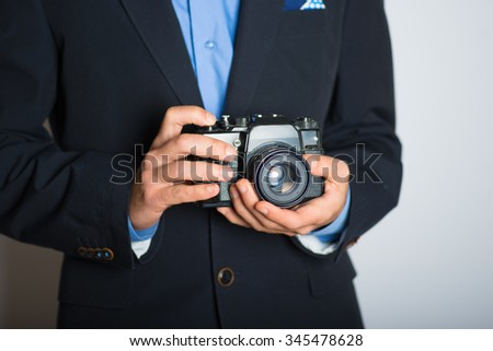 hand with retro, vintage camera. advertising or business concept, isolated on a gray background. - stock photo