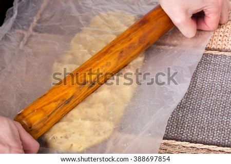 Hand with rolling pin roll out dough for cake. On a table as a background. - stock photo