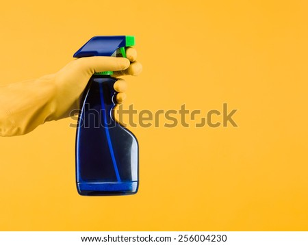hand with rubber glove holding cleaning spray bottle on yellow backgrund. copy space available - stock photo