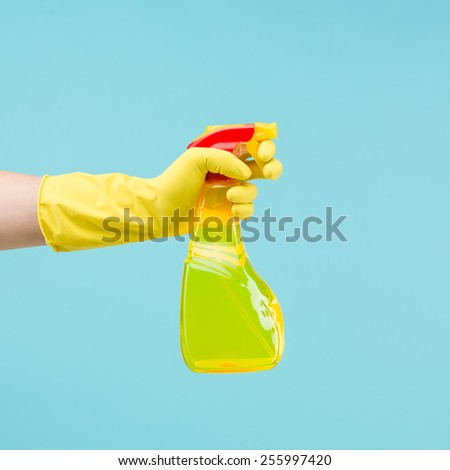 hand with rubber glove holding yellow cleaning spray bottle on light blue background - stock photo