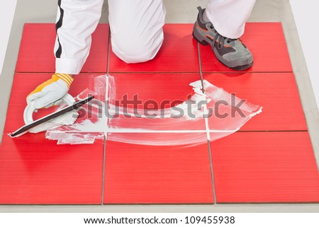 hand with rubber trowel applying grout tile - stock photo