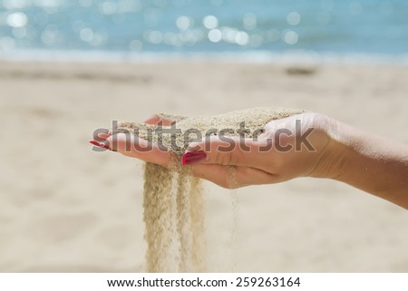 Hand with sand on sea background closeup - stock photo