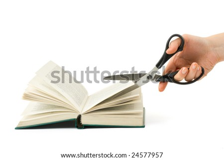 Hand with scissors cutting book isolated on white background