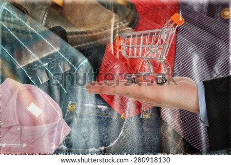 hand with shopping cart against abstract background with men's clothes