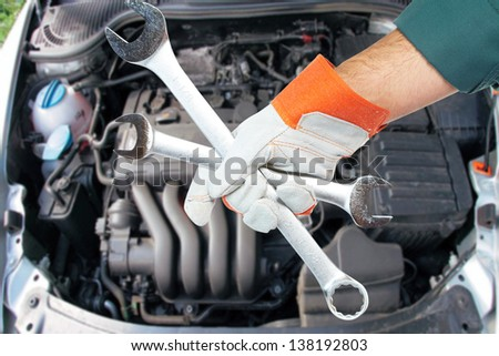 Hand with spanner. Auto mechanic in car repair