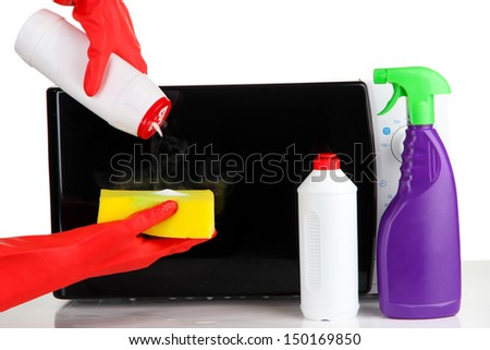 Hand with sponge cleaning  microwave oven, isolated on white - stock photo