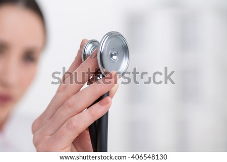 Hand with stethoscope, doctor's face at background. Close up. Side view. Concept of medical examination.