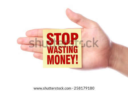 Hand with Stop Wasting Money note is isolated on white background. - stock photo