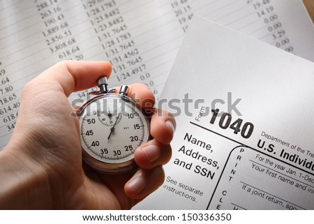 Hand with stopwatch on tax form and budget - stock photo