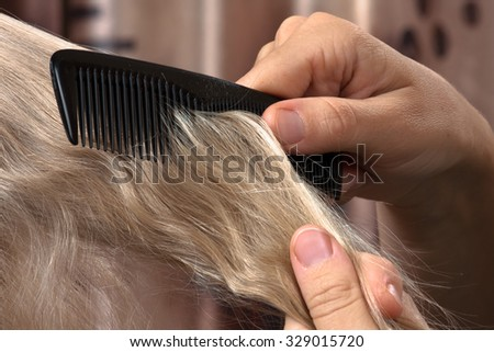 hand with strand of hair and comb