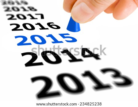 Hand with the game piece taking the next step from the year number 2014 to the next year 2015 - stock photo