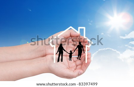 Hand with the silhouettes of the family and house - stock photo