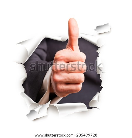 hand with thumb up breaking through wall - stock photo