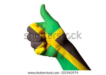 Hand with thumb up gesture in colored jamaica national flag as symbol of excellence, achievement, good, - for tourism and touristic advertising, positive political, social management of country - stock photo