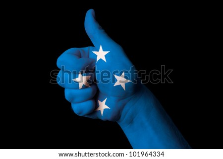 Hand with thumb up gesture in colored micronesia national flag as symbol of excellence, achievement, good, - for tourism and touristic advertising, positive political, social management of country