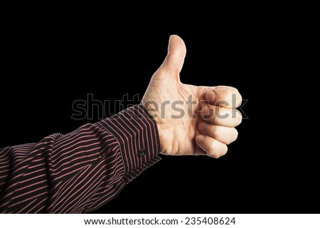 hand with  thumb up on black background - stock photo