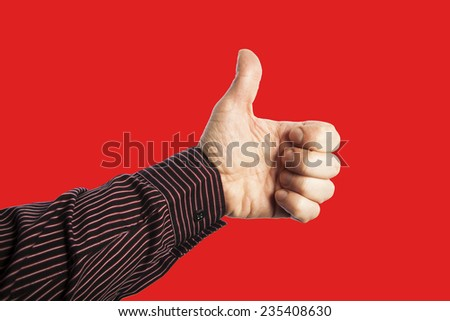 hand with  thumb up on red background - stock photo
