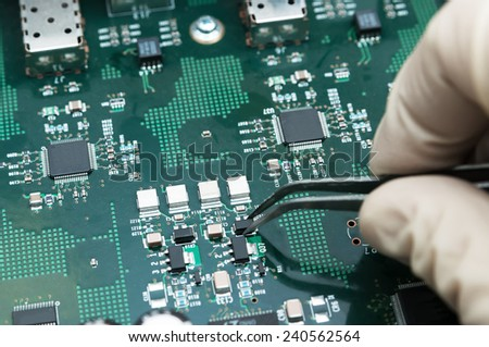 Hand with tongs on a PCB - stock photo