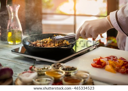 Hand with tongs touches meat. Cut vegetables on cooking board. Add more ingredients to pork. Gourmets will enjoy the taste.