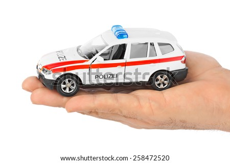 Hand with toy police car isolated on white background - stock photo
