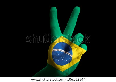 Hand with two finger up gesture in colored brazil national flag as symbol of winning,  - for tourism and touristic advertising, positive political, cultural, social management of country - stock photo