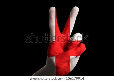 Hand with two finger up gesture in colored england national flag as symbol of winning, - for tourism and touristic advertising, positive political, cultural, social management of country