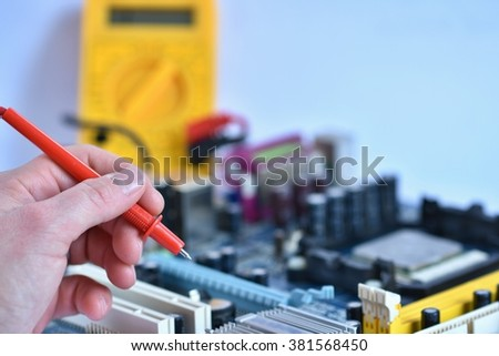 Hand with voltmeter above board with components.  Repair of computers and modern technologies. - stock photo