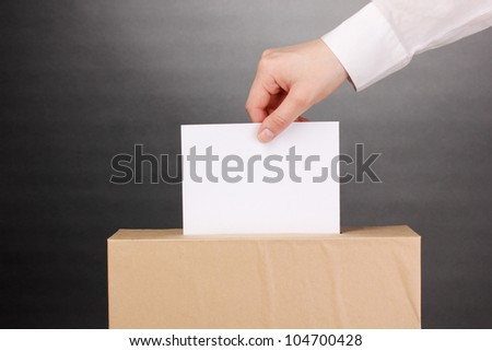 Hand with voting ballot and box on grey background - stock photo