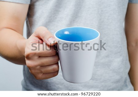Hand with white and blue cup of coffee - stock photo
