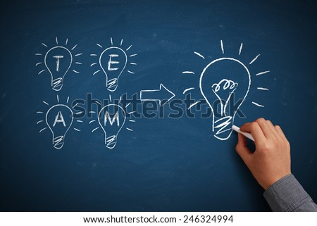 Hand with white chalk drawing light bulbs sketched on chalkboard. Small ideas make a big one. Teamwork concept. - stock photo