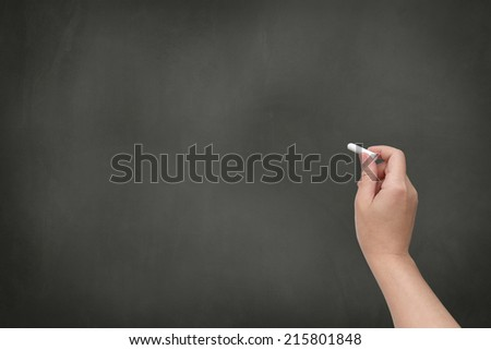 Hand with white chalk on a blank blackboard - stock photo