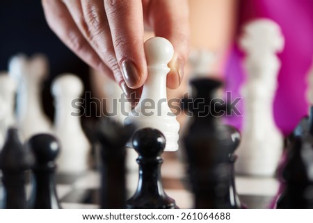 Hand with white pawn over chessboard closeup - stock photo