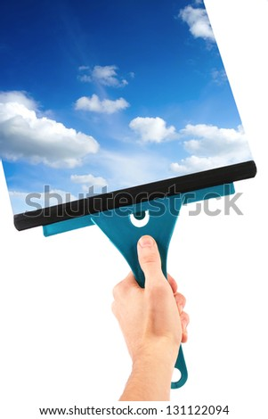 hand with window cleaning tool and blue sky - stock photo