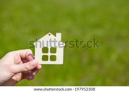 hand with wood house - stock photo